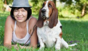 basset hound in park with middle-age woman